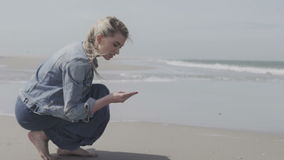 Happy young woman in denim jacket finding something on lonely beach. Portrait of cheerful relaxed young woman on cold beach, autumn time, slow motion stock video