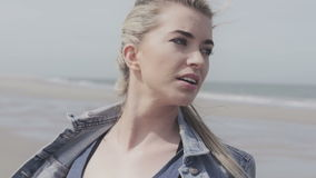 Happy young woman in denim jacket having fun time on lonely beach. Portrait of cheerful relaxed young woman on cold beach, autumn time stock footage