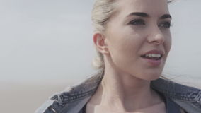 Happy young woman in denim jacket relaxing on lonely beach. Portrait of cheerful relaxed young woman on cold beach, autumn time stock video footage