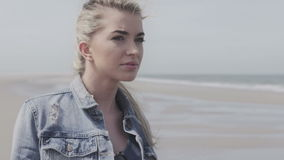 Happy young woman in denim jacket relaxing on lonely beach. Portrait of relaxed young woman on cold autumn beach stock video footage