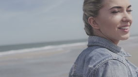 Happy young woman in denim jacket smiling to the camera on lonely beach. Portrait of cheerful relaxed young woman on cold beach, autumn time stock footage