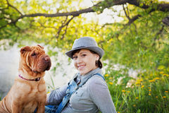 Happy young woman in denim overalls and hat with red cute dog Shar Pei sitting in the field near the lake at sunset Stock Photo