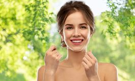 Happy young woman with dental floss cleaning teeth stock photos