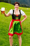 Happy young woman in a dirndl with a beer Royalty Free Stock Images