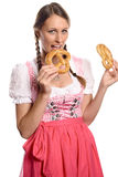 Happy young woman in a dirndl eating pretzels Stock Images