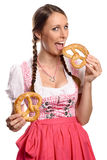 Happy young woman in a dirndl eating pretzels Stock Photo