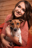 Happy young woman and dog at Christmas. Happy young woman and dog at home with christmas tree Royalty Free Stock Photo