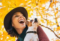 Happy young woman with dog outdoors in autumn Royalty Free Stock Photos