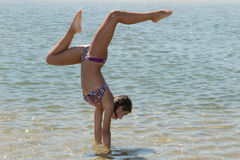 Happy young woman doing cartwheel on the beach bikini Stock Image