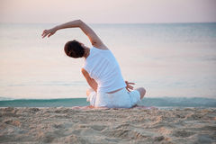 Happy young woman doing exercises sitting on sea coast Royalty Free Stock Photography