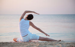 Happy young woman doing exercises sitting on sea coast Stock Photography