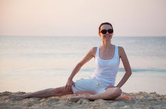 Happy young woman doing exercises sitting  on a sea coast Royalty Free Stock Photo