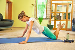 Happy young woman doing fitness at home. Stock Image