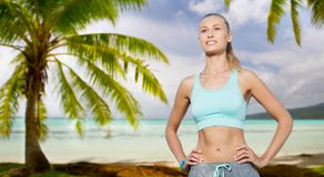 Happy young woman doing sports outdoors. Fitness, sport, friendship and healthy lifestyle concept - happy young woman doing sports over tropical beach background Stock Photos