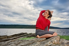 Happy young woman doing yoga exercise outdoors on the stone near river. Sporty woman dressed in the sportwear and barefoot. Beautiful landscape like a Royalty Free Stock Image