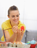 Happy young woman drawing on Easter red egg Stock Images
