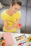 Happy young woman drawing on Easter red egg Stock Photography