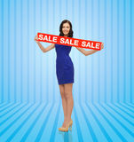 Happy young woman in dress with red sale sign Royalty Free Stock Image