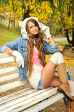 Happy young woman dressed in a white bear hat. Happy young woman dressed in a white bear hat resting in autumn park royalty free stock photo
