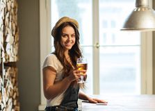 Happy young woman drinking beer at bar or pub. People, drinks, alcohol and leisure concept - happy young redhead woman drinking beer at bar or pub royalty free stock images