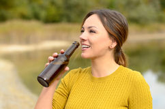 Happy young woman drinking beer at a picnic Royalty Free Stock Images