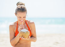Happy young woman drinking coconut milk on beach Stock Photos