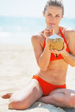 Happy young woman drinking coconut milk on beach Royalty Free Stock Image