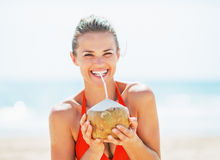 Happy young woman drinking coconut milk on beach Royalty Free Stock Photos