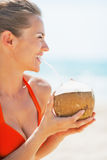 Happy young woman drinking coconut milk on beach Stock Photography