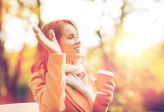 Happy young woman drinking coffee in autumn park Royalty Free Stock Photo