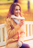 Happy young woman drinking coffee in autumn park. Season, hot drinks and people concept - beautiful happy young woman drinking coffee or tea from disposable Stock Photography