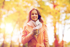Happy young woman drinking coffee in autumn park. Season, hot drinks and people concept - beautiful happy young woman drinking coffee or tea from disposable Stock Images