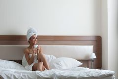 Happy young woman drinking coffee in bedroom Royalty Free Stock Photography