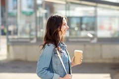 Happy young woman drinking coffee on city street Royalty Free Stock Photo