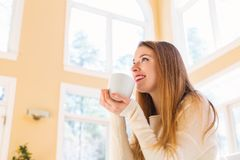 Happy young woman drinking coffee Royalty Free Stock Photography