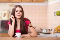 Happy young woman drinking coffee at home Royalty Free Stock Photos