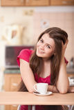 Happy young woman drinking coffee at home Stock Photography