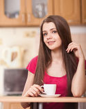 Happy young woman drinking coffee at home Royalty Free Stock Image