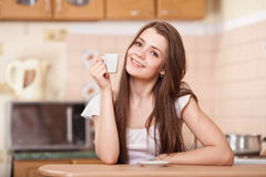 Happy young woman drinking coffee at home Royalty Free Stock Photo