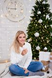 Happy young woman drinking coffee in living room with decorated stock photos