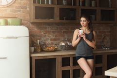 Happy young woman drinking morning coffee in kitchen Stock Photos