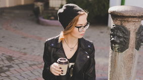 Happy young woman drinking coffee and relaxing outdoor, smiling and looking away from camera stock video footage