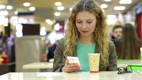 Happy young woman drinking coffee or tea and using mobile phone in a coffee shop stock footage