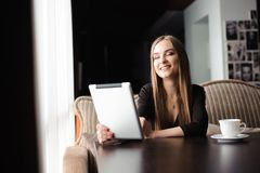 Happy young woman drinking coffee, tea and using tablet computer in a coffee shop royalty free stock photo