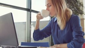 Happy young woman drinking coffee and using tablet in a coffee shop stock footage