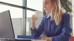 Happy young woman drinking coffee and using tablet in a coffee shop.  stock footage