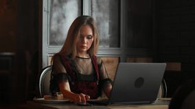 Happy young woman drinking coffee and using tablet computer in cafe.  stock footage