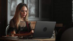 Happy young woman drinking coffee and using tablet computer in cafe stock footage
