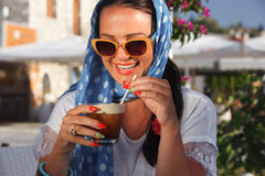 Happy young woman drinking iced coffee in restaurant Stock Photo