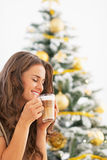 Happy young woman drinking latte macchiato near christmas tree Stock Photos
